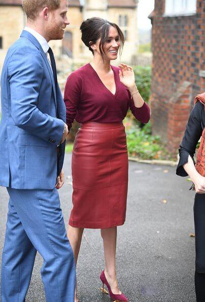Meghan Markle wore Joseph pullover, Hugo Boss Selrita leather skirt, Sarah Flint pumps and Emily Mortimer Hera gold and diamond earrings