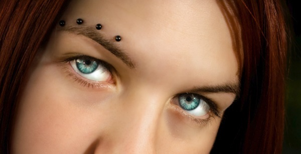 a row of rocking eyebrow piercings