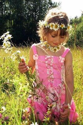 Foto anak perempuan kecil bermain bunga