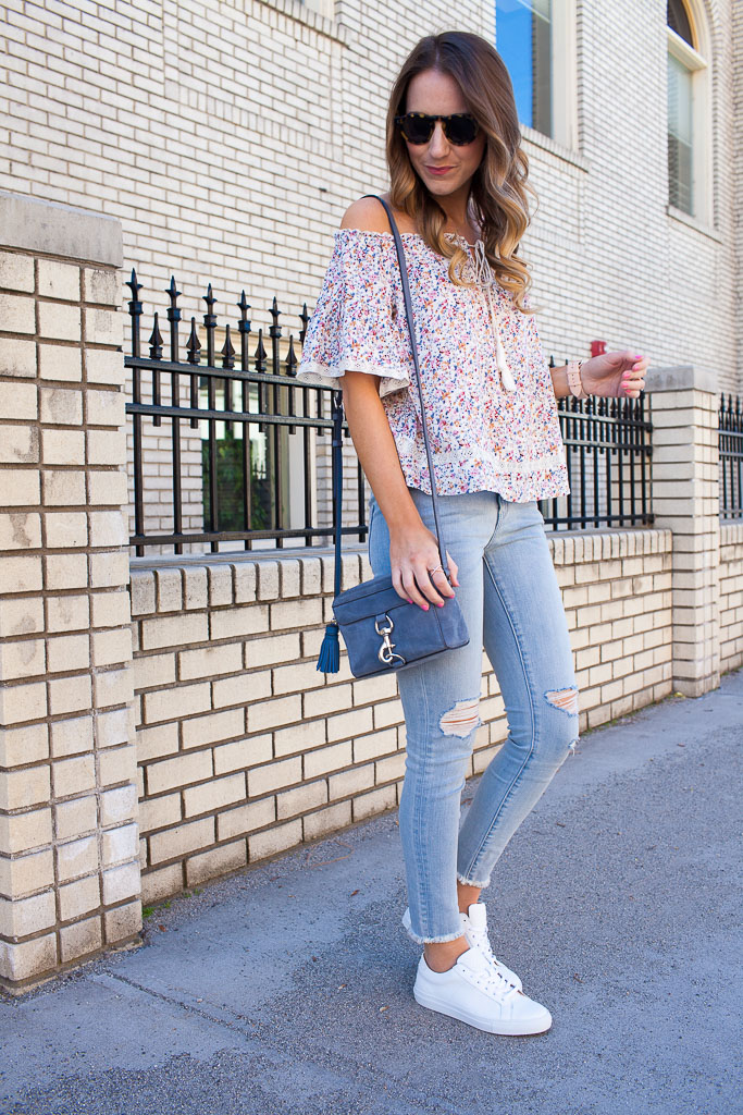 Styling white sneakers for spring with distressed denim and a floral off the shoulder top.