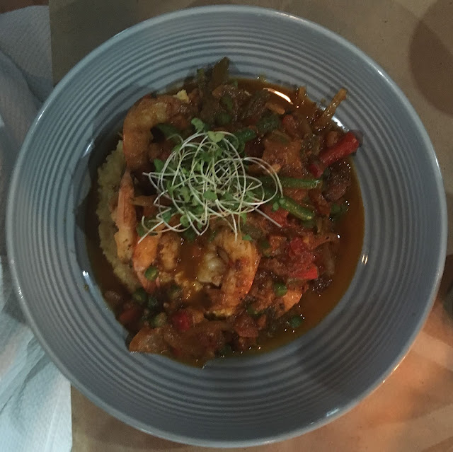 reddish colored grits topped with shrimp and sprouts in a gray bowl
