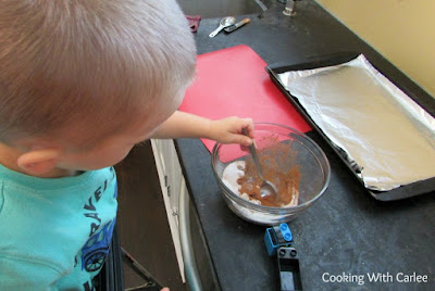 kid stirring together spice mixture for nuts