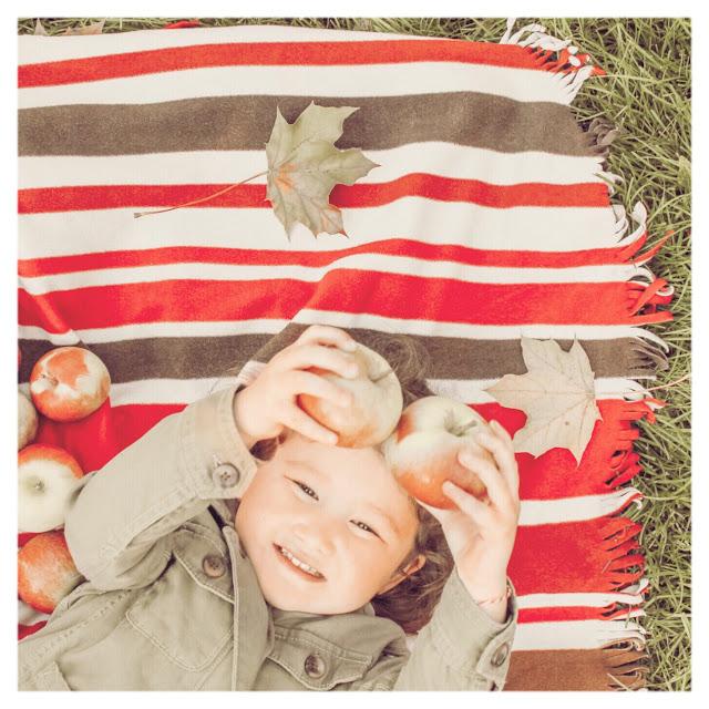 little girl holding up apples