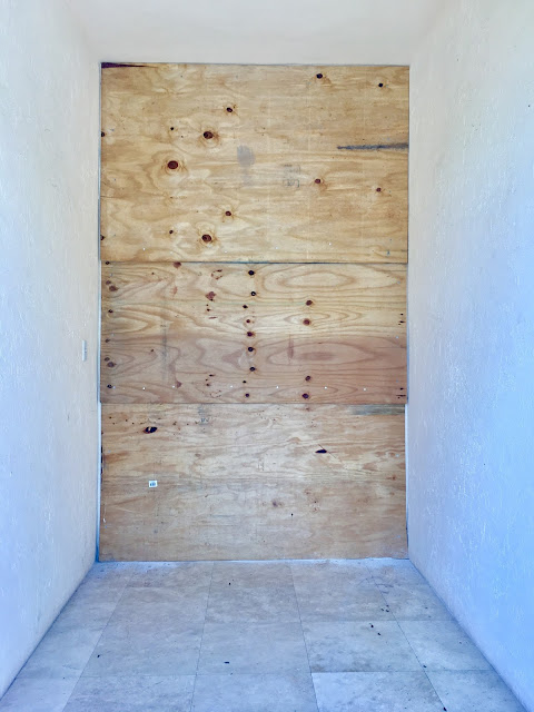 Photo of plywood covering the door and other windows at the entrance to my house.