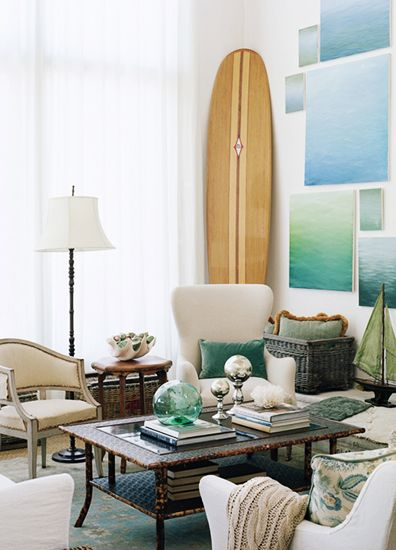 Beachy living room by Giannetti Home with water inspired paintings and surfboard - found on Hello Lovely Studio