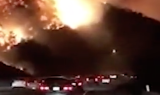 Highway to Hell! Terrifying video shows drivers on their way to work in LA passing hills covered with flames in the midst of raging wildfires