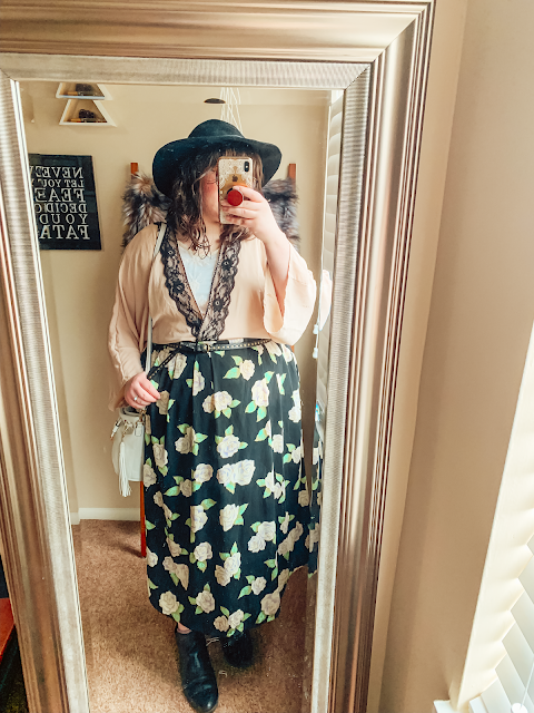 A mirror selfie of an outfit of a wide brim black felt floppy hat, a pink kimono with black lace trim over a white lace blouse to look like a wrap top, tucked into a black skirt with graphic florals.