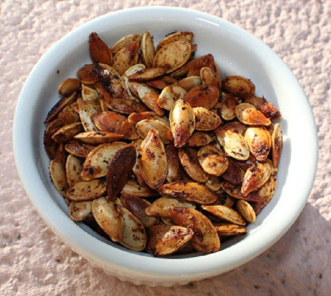These are pumpkin seeds that were raw and then roasted with Italian seasoning. This is how to roast pumpkin seeds and make them from scratch by using a sugar pie pumpkin after carving from Halloween. These pumpkin seeds are in a white round bowl and have a crispy outside shell and ready to snack on.