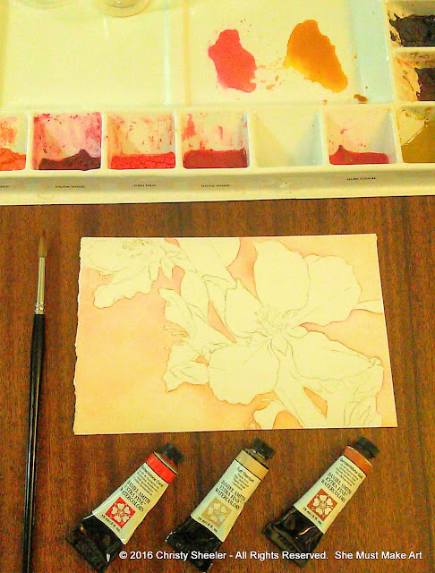 One of the cherry blossoms watercolor paintings in its beginning stages.  The three tubes of watercolor used for the background.