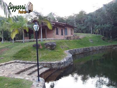 Muro de pedra, com pedras rústicas, em volta do lago junto a cabana rústica com toras de eucalipto tratado com as paredes de tijolo a vista e a escada de pedra no lago. Muro de pedra em Piracaia-SP.