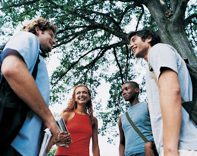 Picture of 4 students outside smiling and laughing. Trees in background.