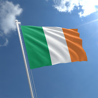 The green, white and organe flag of the Republic of Ireland on a white pole against a blue sky with white clouds.