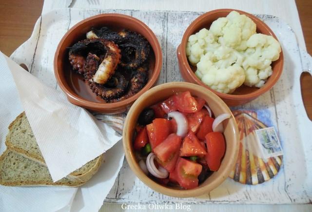 na tacy grillowana ośmiornica, greckie pomidory, kalafior, gliniane naczynia z jedzeniem, chleb
