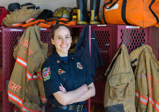 A female firefighter poses for a photo in front of lockers with fire gear