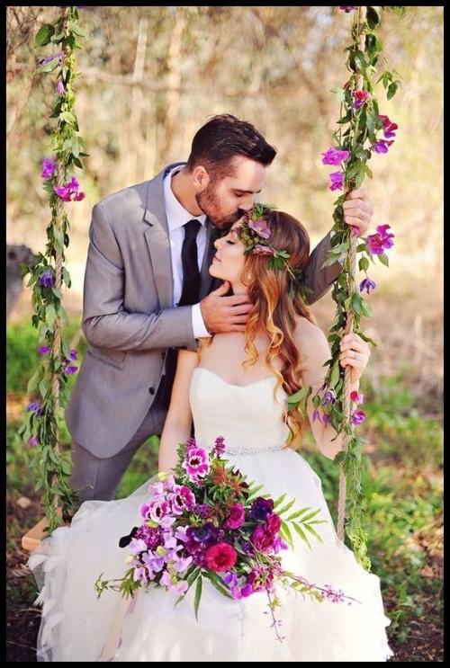 Casal de noivos. A moça sentada em um balanço com flores e o rapaz fazendo carinho.