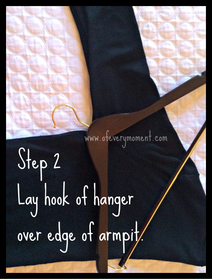 How to hang a sweater: Step 2. Lay a hanger down with the hook poking out of the armhole area