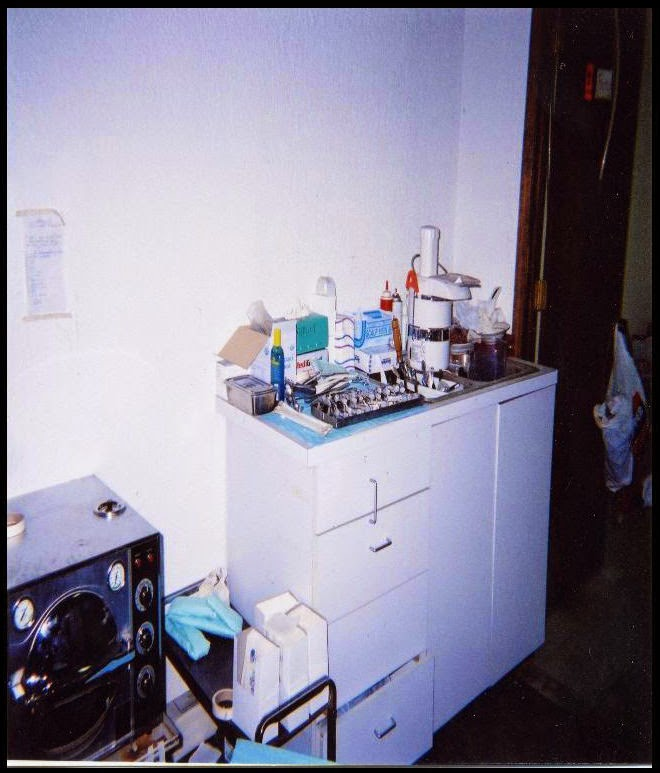 Freestanding cabinet with cluttered countertop. Amid the clutter is a food processor. Nearby is an autoclave.