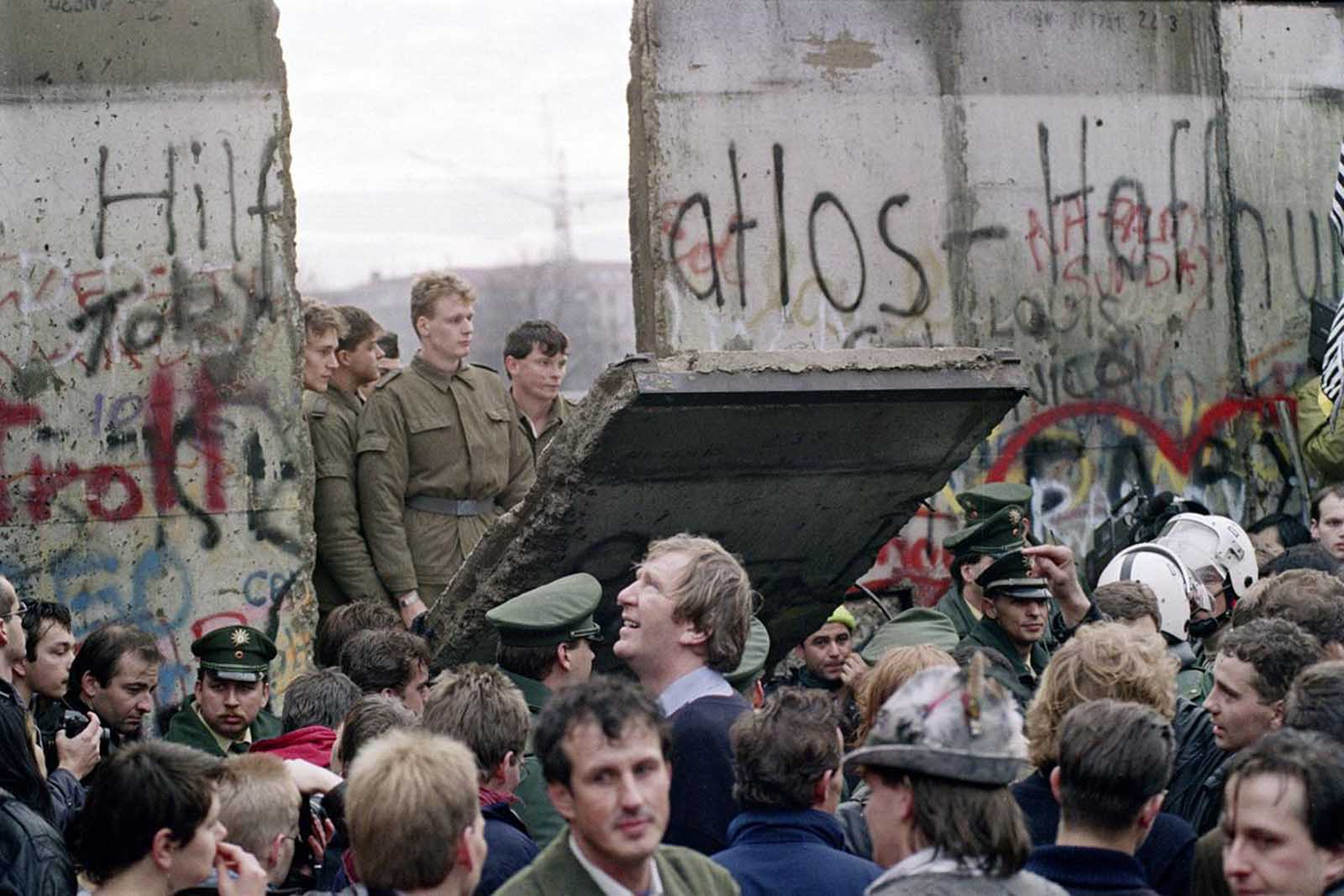 West Berliners crowd in front of the Berlin Wall early November 11, 1989 as they watch East German border guards demolishing a section of the wall in order to open a new crossing point between East and West Berlin, near the Potsdamer Square.