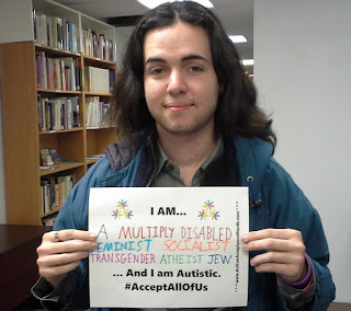 "Image: Me in front of a book shelf, holding a sign which says ""I am... A multiply disabled feminist socialist transgender atheist jew ...and I am Autistic. #AcceptAllOfUs"""