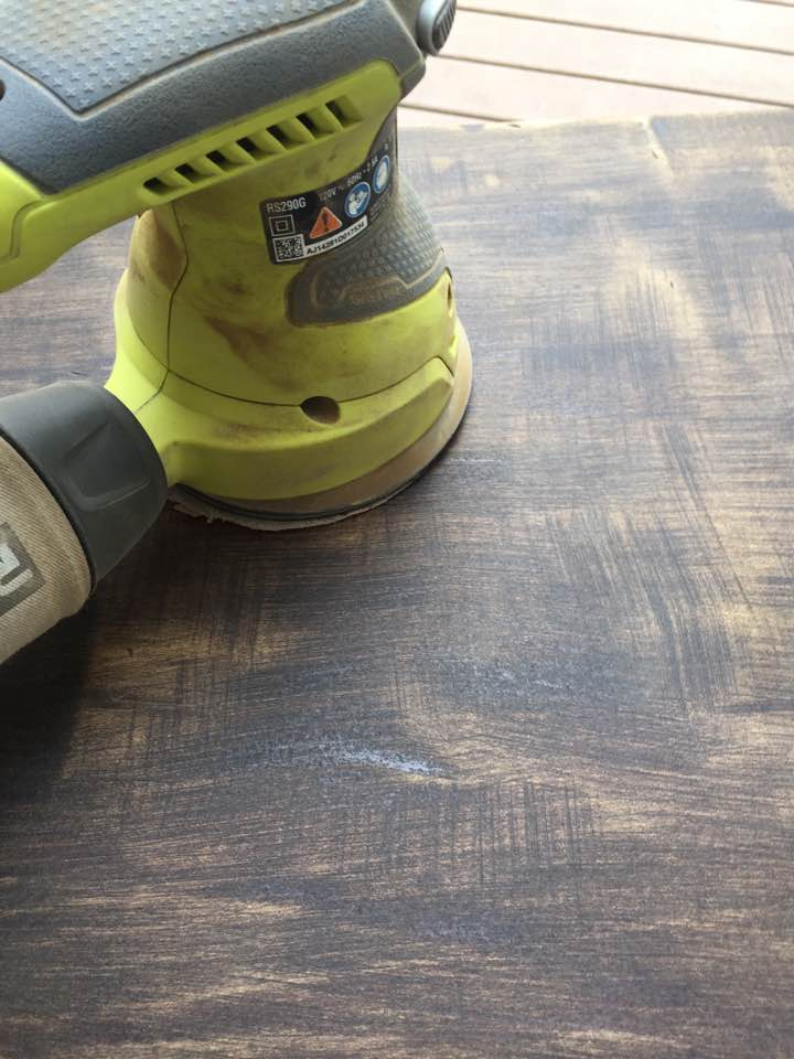 An orbital sander quickly removes the old finish.