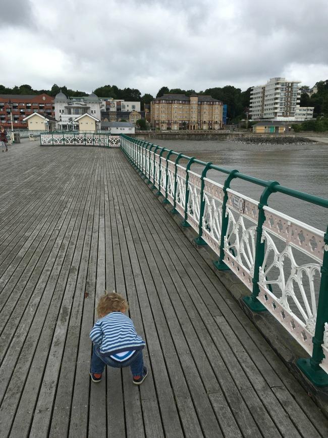 Penarth-pier-toddler-looking-through-boards-at-sea