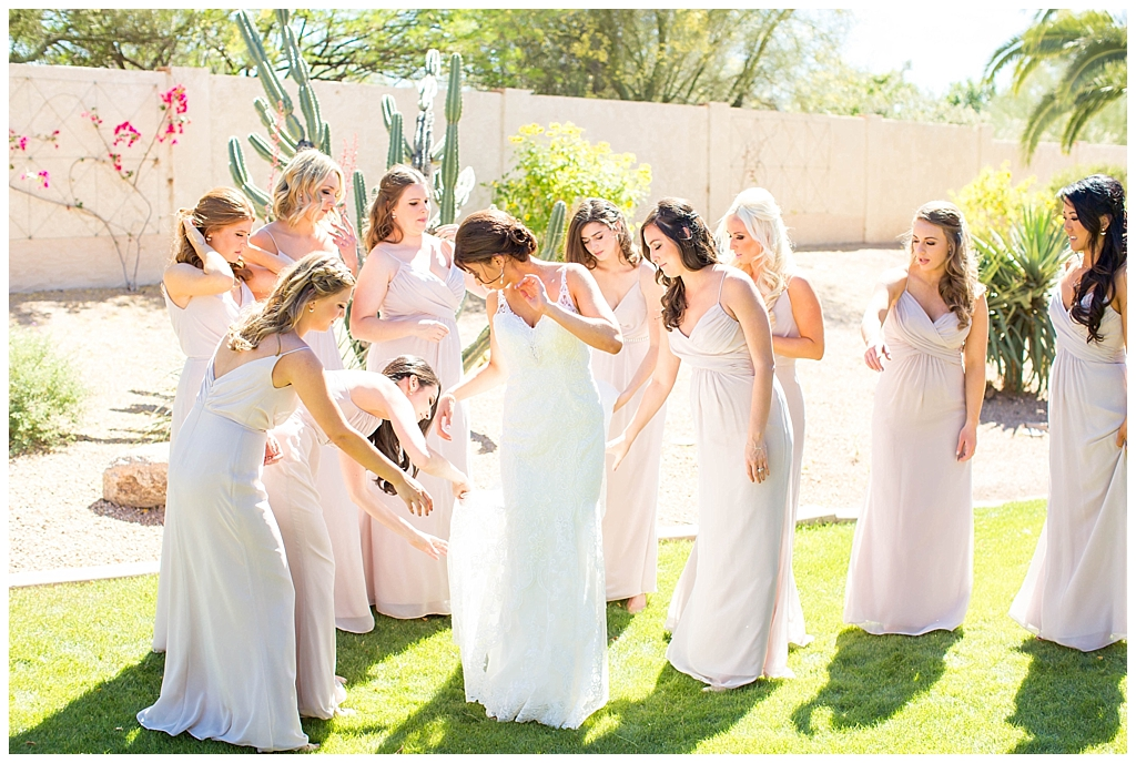Bride getting ready with bridesmaids in blush dress