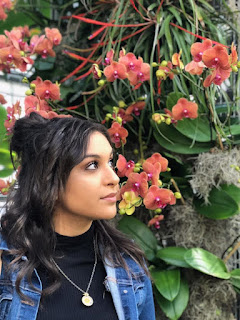 Image of Neveen Shawish standing in front of a large orchid with salmon colored blossoms. She looks at the flowers, and is wearing a black, mock turtle neck top with a jean jacket, and a large gold pendant necklace. She has long, wavy chestnut brown hair and brown eyes.