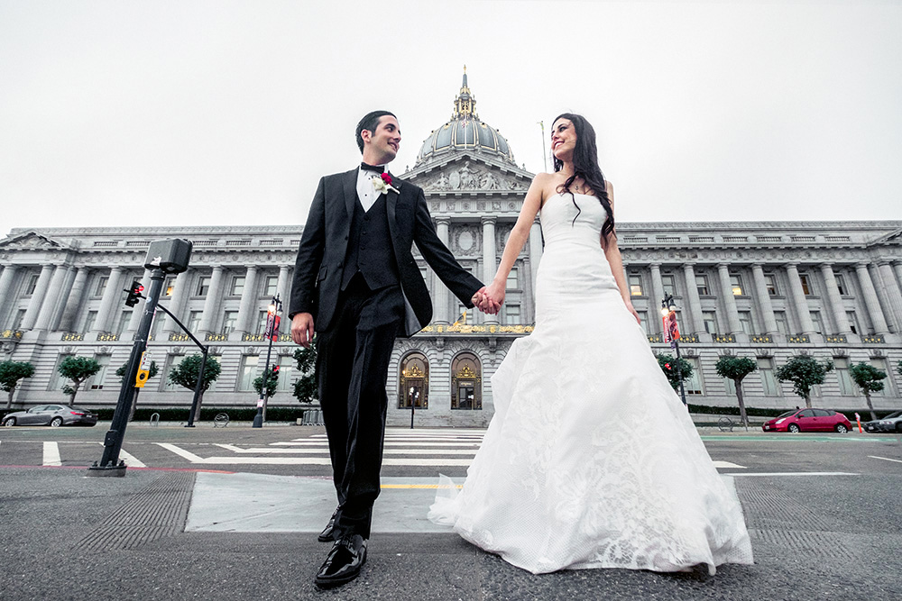 Bride and groom walking out San Francisco City Hall