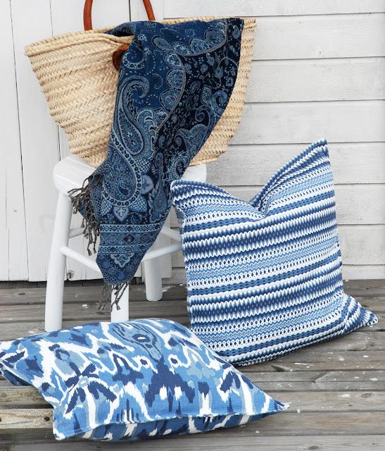Somriga kuddar i blått och vitt och pläd med paisleymönster.
