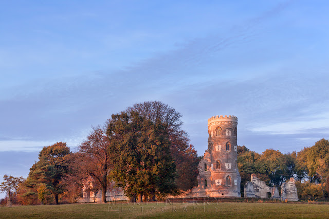 Autumn coloured trees and Folly are bathed in evening light on the Wimpole Estate