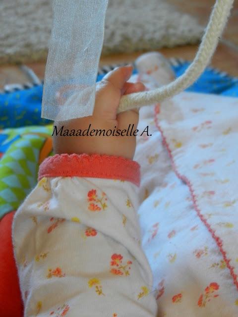 || Lacets, cordelettes, rubans ; un portique pour bébé gai et coloré