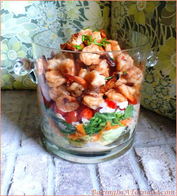 Layered Thai Shrimp Salad uses leftover Thai marinated shrimp, mixed with cool crisp vegetables topped with a parmesan dressing for a flavorful summer meal. | Recipe developed by www.BakingInATornado.com | #recipe #shrimp #dinner