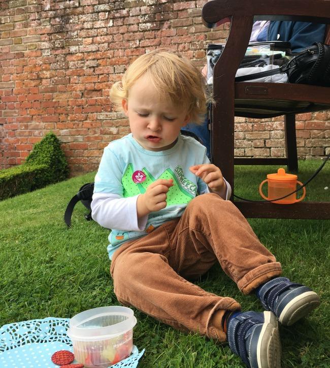 toddler-eating-heavenly-tasty-organic-crispy-veggie-waffles-on-paper-doilly