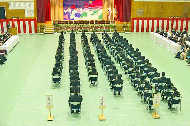 stage, auditorium,students, rows of folding chairs, uniforms