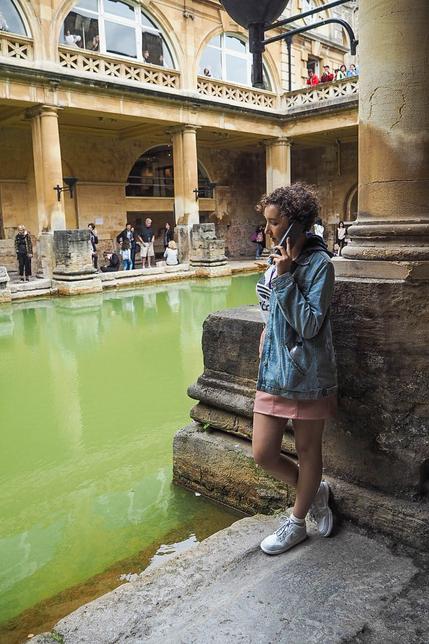 Listening to audio guide at Roman Baths in Bath