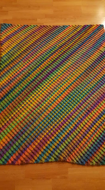A close up of Meredith's corner to corner blanket.  The long colour changing yarn creates diagonal stripes of varying widths.  Working the rows on the bias (from corner to corner) gives the blanket excellent drape.
