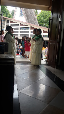 waiting blessing from priest by the children in the isle