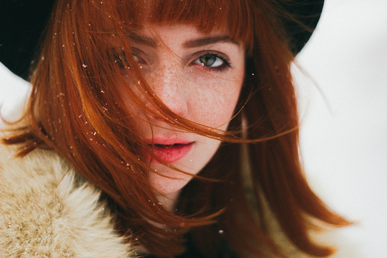 ginger girl with pale skin and freckles in black hat and fur coatat winter