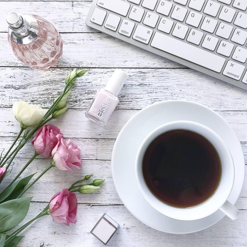 filiżanka kawy, perfumy, lakier do paznokci, kwiaty i klawiatura na tle białych desek