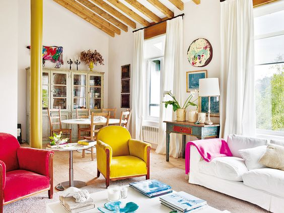 Colorful velvet chairs add color pop in rustic living room