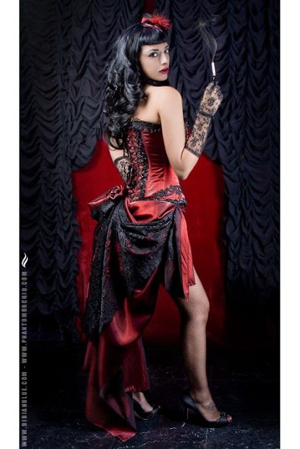 Steampunk showgirl, steampunk burlesque and steampunk pin-up costumes and clothing for women. Red and black corset, bustle skirt with train, black lace gloves, fishnet stockings, red fascinator, cigarette holder