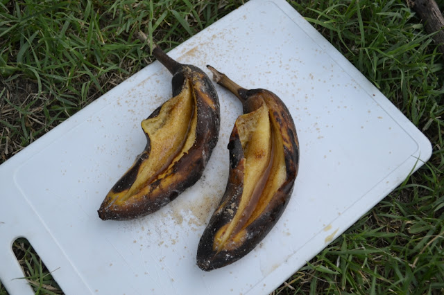 2 opengesneden bananen met schil van de barbecue met in de opening een scheut rum en wat vanillesuiker