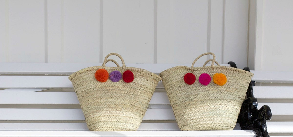 moroccan pom pom woven basket bags in purple and pink