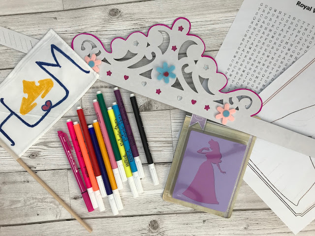 Flatlay showing felt tips, a wordsearch, princess stencils and a crown and flag decorated