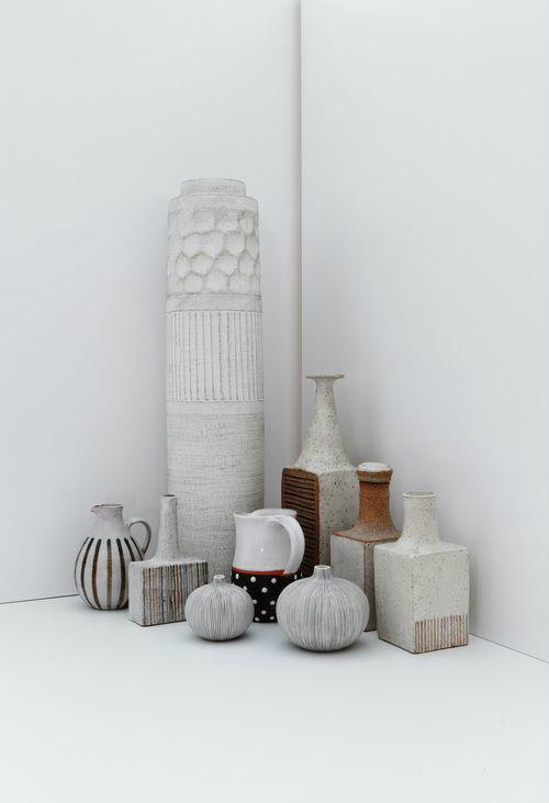 Mehrere weiße Vasen in unterschiedlichen Höhen und Formen stehen in der Ecke eines Raumes