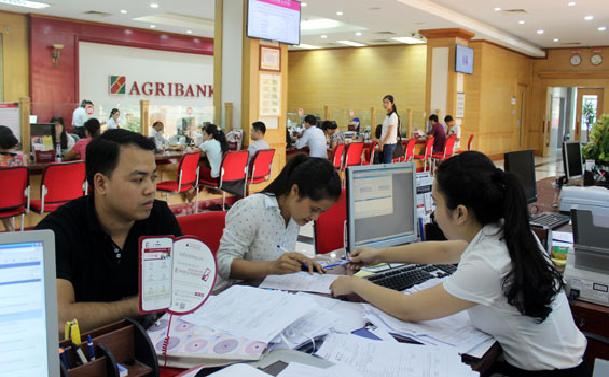 Nhân viên ngân hàng ở Hà Nội hướng dẫn khách hàng vay vốn