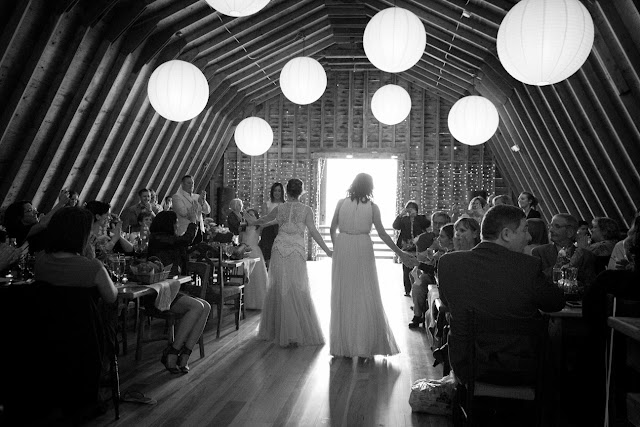 The brides entering their barn reception at Jonna and Heather's Inn at West Settlement Wedding by Karen Hill Photography