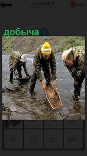 На реке старатели производят добычу лотками, вероятно золота