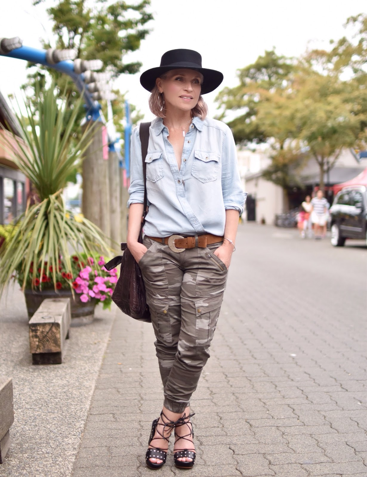 Monika Faulkner personal style inspiration - camo pants with a chambray shirt, lace-up sandals, and a flat-top fedora