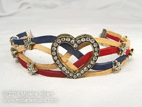 Suede leather lace bracelet in shades of cranberry red, sand and cadet blue create the stripes dotted with silver star beads. The focal is a crystal studded heart slider bead.